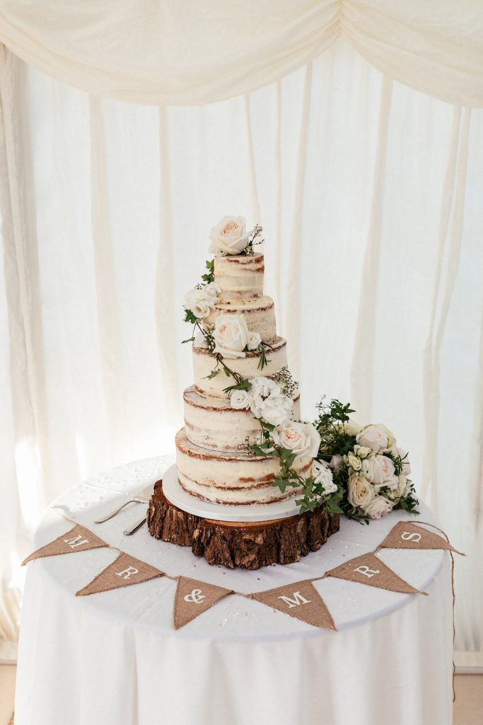 naked wedding cake with fresh flowers by holly & ivy flowers